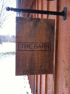 Personalized sign hanging from metal post. Painted on barn