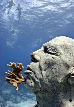 """Underwater Museum (Cancun) -Divers swim near Jason de Caires Taylor's """"The Man on Fire,"""" one of several sculptures immersed in the water off Cancun."""