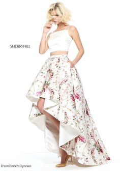 Sherri Hill 51205 is a 2-piece prom dress with a solid colored, spaghetti strapped crop top and a floral print high low skirt.