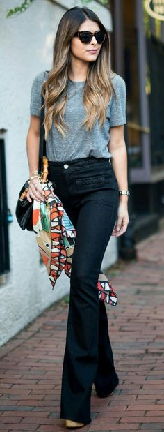 Simple. Gray tee worn with flared dark indigo wash jeans (can read black) and platform espadrilles. Oversized sunnies, black shoulder bag and colorful patterned scarf tied around it. Watch, bracelets. Minus the scarf it is minimalism personified. Style Planet