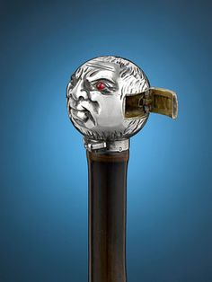 The intimidating visage of the Man in the Moon stares out from the silver handle of this intriguing match holder cane. If one looks past the furrowed brow, smirk and menacing red eyes, one will find a hidden compartment for one's matches. This incredible piece is set atop a shaft of polished bamboo. Match holders, also known as match safes or vesta cases are highly collectible. To find one as the handle of a walking stick is a rare pleasure.  Circa 1880