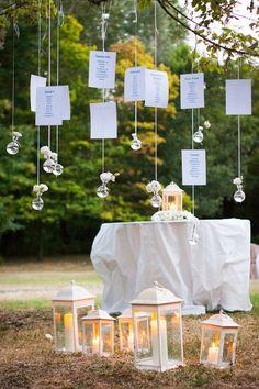 Idea romantica per un tableau matrimonio elegante nei toni del bianco: lanterne bianche decorano il prato e da una pianta pendono fili con vasetti in vetro per fiori e foglietti con i nomi dei tavoli