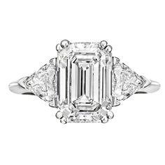 Contemporary Emerald-cut diamond engagement ring in platinum with trillion-cut diamond side stones.
