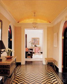Striking herringbone floor in this entryway; via Elle Decor and photographed by William Waldron.