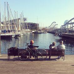 Ciclista tocando la guitarra con pareja mirando el puerto en #Barcelona