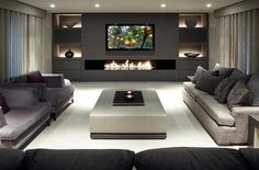 Modern Chic Media Room...gorgeous upholstery... Love the fireplace and beautiful candle lighting in table.
