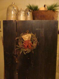 Prim Blue Cupboard...with rustic wreath...olde crocks & basket filled with pine.