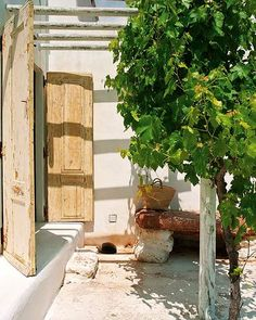 Bleached doors and dappled vine shade.    from homebunch.com