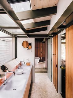 Fung   Blatt designed the master bathroom vanity, which features Agape washbasins and fixtures and an angled mirror that reflects the oak trees seen through the skylights.