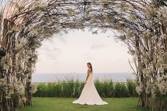 Floral arch with baby's breath and branches // Judd and Sonya's Classic White Bali Wedding