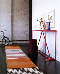 By piecing together small floor mats you can make a runner in your price range with a one-of-a-kind design!Depending on your hallway, pick out a few two by three-foot cotton or wool flat-woven rugs. Choose simple geometric patterns and stick to one color scheme. Iron the rugs to flatten them. Arrange them face down, seams perfectly aligned. Cover each seam with duct tape, or if  if you are a stitcher, sew them together with a hooked carpet needle and nylon carpet thread.