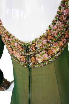 Pierre Balmain couture evening gown 1960s green silk chiffon layered over a pale pink base. The effect of the two colors together is quite beautiful. The bodice, cuffs and hem are extensive and heavily embroidered beaded sequined with pink, gold and clear beads and baubles all perfectly and meticulously done. It is an amazing example of the fine workmanship and attention to detail of couture.