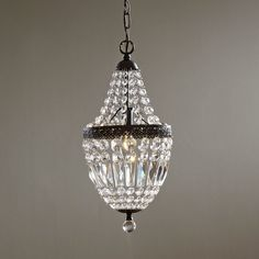 Draped with sparkling crystals, the Evelynne Chandelier makes a big impact on a small scale. Bronze-finished, embossed metal completes the classic look.