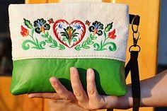 Srdénko Clutch taštička len tak do ruky. S folkovou výšivkou na doma tkanom plátne kombinovaná s koženkou. Taštička je podlepená ronarom a podšitá bavlnenou látkou . Na podšívke su vypracované 2 vrecka zipsové a nakladané spolu s karabinkou na kľúče. Zapína sa na zips. 19 x 25 cm 20 €