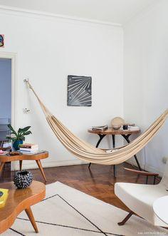Sala de estar minimalista tem rede de balanço e seleção de peças vintage.