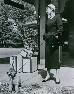 "The actress Audrey Hepburn (as Sabrina Fairchild, with the Poodle called ""David"") photographed at the train station of Glen Cove, a city in Nassau County (a suburban county on Long Island), in the state of New York (USA), during the filming of her new movie ""Sabrina"", in October 1953.Audrey was wearing:Suit: Givenchy (of black wool, short coat, collarless, buttons of black resin creating a geometric motif as an ornamental detail, and skirt in a straight line, both pieces lined with silk, of…"