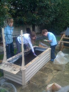 How to prepare a raised vegetable bed. Easy....make sure you hire plenty of kids from the local nursery. :-) Put one layer of newspaper; couple sheets, wet with water, 1 layer compost ~ 10cm, 1 layer snowpea mulch ~ 10cm, one layer top soil ~10cm then repeat. You can use seed raising mix instead of top soil especially for last layer.