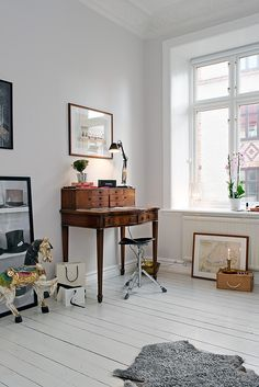 A wooden writer's desk, a unique carousel horse, and vintage artwork add charm to the bedroom. Source: Alvhem Estate & Interior