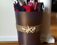 Here is another DIY umbrella holder that you can make using a trashcan. Instead of a paint and stencil maneuver, you can embellish the umbrella stand you make. This coastal cutie offers you plenty of inspiration; you can embellish an umbrella stand using items you already have in your home.