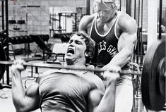 ILYKS.COM - Arnold Schwarzenegger letting out some steam as he presses weight above him while working out his deltoids Working the shoulders