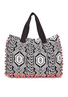 This tribal stitch tote bag features contrast pom pom details, making this piece perfect for your collection.