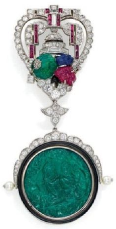 AN ART DÉCO MULTI-GEM LAPEL BROOCH. The heart-shaped surmount set with diamonds, rubies, carved emeralds, rubies and sapphires, suspending a swiveling pendant centring an emerald cameo depicting the Indian God Krishna serenading his love Radha with his flute, the reverse carved with a stylised poppy flower, within a black enamel surround and pearl shoulders, 1920s. #ArtDeco #vintage #brooch
