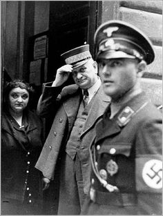 An SS officer in Vienna standing at the entrance to the Jewish community building, undated. Two faces to remember -- doorman and woman standing next to him.