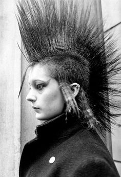 [B/w profile photo of a person with a tall mohawk and buzzed sides, with long crimped sidelocks before and behind the ear and eyeshadow that extends to a point at the temples]