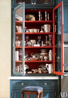 The interior of a cabinet in designer J. Randall Powers's Houston kitchen is painted a bold red.
