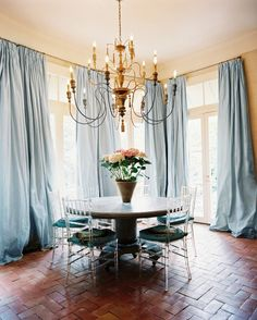 these curtains Love this breakfast room with the brick floor, lucite chairs, fab chandy, and flowing drapes. Lucite Chairs, Lucite Furniture, Chiavari Chairs, Bamboo Chairs, Acrylic Furniture, French Furniture, Furniture Decor, Blue Drapes, Silk Curtains