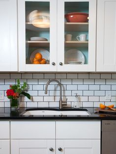White subway tile and white cabinets with glass doors make for a sleek, simple workspace around the sink of this contemporary kitchen.