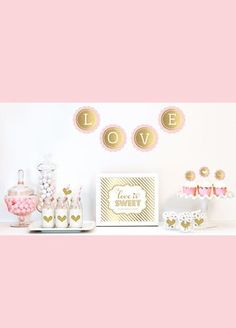 """Celebrate your special event with a little glitz and glamour with our Gold Glittering Decor Kit. Each Kit includes metallic foil and glittery gold items such as banners, stickers and cupcake toppers for dressing up your dessert and candy buffet table. Items in party kit are not personalized and some assembly is required. Kit Includes: 1 Metallic Foil Scallop Banner spelling out LOVE as shown. 1 Metallic Gold Table Sign printed with """"Love is Sweet, Please Take a Treat"""". 25 Striped Straws."""