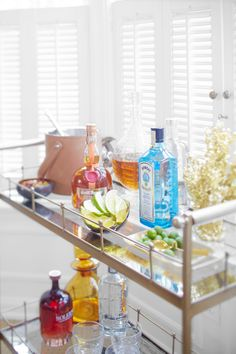Bar carts serve as stylish yet hardworking hubs for entertaining. Learn how to style your beverage station with these beautiful bar cart ideas. #barcart #barcartstyling #barcartideas #barcartdecor #bhg Bar Cart Styling, Bar Cart Decor, Outdoor Bar Cart, Vintage Bar Carts, Black Table Lamps, Wooden Bar, Better Homes, Bars For Home, Traditional House