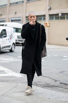 """Korean model Sung Jin Park wears a black coat Cav Empt tshirt and adidas YEEZY Boost 350 """"Oxford Tan"""" shoes during New York Fashion Week Men's..."""