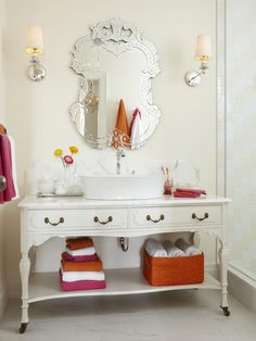 For this cottage-style bathroom, designer Sarah Richardson chose a pair of glitzy mirrored sconces, instead of a standard bar-style vanity light, to flank the Venetian mirror. Not only do the sconces work beautifully in this feminine space, they're also a great choice for lighting the vanity area because they provide even cross lighting with minimal glare.