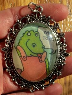 Retro Sweet Pickles Me Too Iguana Pendant  Antique Silver Pendant with bail loop measures 67 x 50 mm   Vintage Artwork under glass dome measures 30 x 40 mm.  This image is from the 1978 Sweet Pickles
