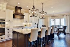 White kitchen with cream bar stools and mini candle pendant lights. Kitchen with mini candle pendant lights over white kitchen island with granite countertops