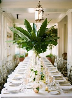 palm leaf wedding tablescape with gold tones in flatware guest chairs and place settings / http://www.deerpearlflowers.com/tropical-leaf-greenery-wedding-decor-ideas/