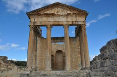 """Dougga Capitol. Dougga is sometimes called """"the best-preserved Roman small town in North Africa"""". Amongst the most famous Roman monuments at the site are a Punic-Libyan mausoleum, the theatre and the capitol. The capitol is a Roman temple from the 2nd century CE, principally dedicated to the three most important Roman gods: Jupiter, Juno and Minerva."""