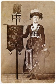 Early marketing: This woman models coffin accessories. The rings dangling from her hat are from coffin robes and could also be used as less expensive handles. Hanging on her dress are coffin chains and a full-sized frame to indicate that this coffin maker also made frames. She wears two coffin plates, one around her neck and the other on her chest flanked between two coffin handles. Coffin plates were often inscribed with genealogical information and then removed and passed on to the family.