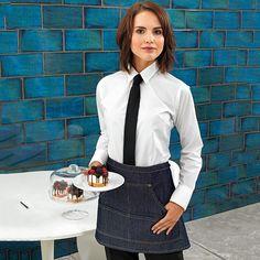 An alternative way to style our new black denim cropped apron. Dressed up or down, this is a style staple for your workforce #Premier # PremierWorkwear #Denim #Apron #StylishStaff #DressingYourWorkForce #DressToImpress #Hospitaility #IndustryWear #Uniform #Bar #Restaurant