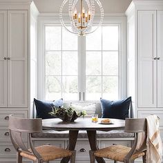 Gorgeous breakfast nook with a window seat lined with extra-plush pillows. Love all the extra storage in the built-ins.
