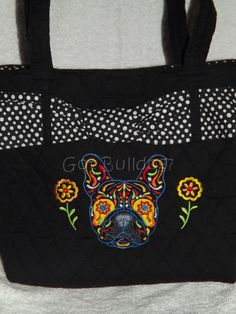 """Beautiful Embroidered Sugar Skull French Bulldog Quilted Tote Bag. Accessorize your life with this fun and classy Black & White Quilted Tote Bag. Featuring a black & white polka dot ribbon. Length: 9"""" Width: 4"""" Height: 9""""  Fiber: 65% Polyester & 35% Cotton Zipper pocket inside"""