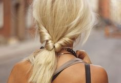 First throw your hair into a loose low ponytail. Then spread the hair above your hair tie into two sections and loop the ponytail through it. Pull it all the way through and loosen up the twisted sides.