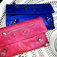 two matching Balenciaga clutches