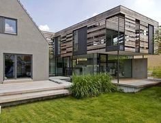 Auch für Bestandserweiterungen sind Architektenhäuser zu empfehlen: Das traditionelle und massive Siedlerhaus wird von dem Neubau in Beton- und Holzständerbauweise optimal ergänzt.