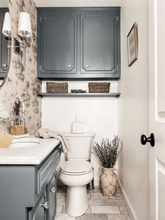 The secret to decorating a bathroom that still has that cozy home vibe? Pair a dark cabinet color with timeless details, like wallpaper and dry florals. This space uses Irony, a gray paint by Clare.