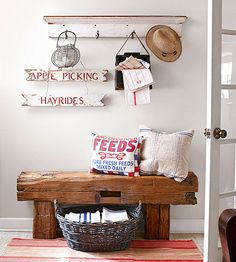 Hand-carved beams salvaged from a collapsed barn create this entryway bench that serves as a convenient seat to slip off muddy shoes. The woven basket and sign are flea market finds; the pillow covers are made from feed sacks. Decor, Decor Styles, Furnishings, Cabin Decor, Barn Wood, Barn Beams, Farmhouse Style Table, Rustic Bench, Home Decor