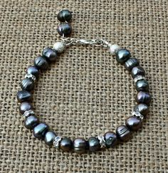 Steel Gray Cultured Freshwater Pearls Bracelet with Dangle $15.00 This+gorgeous+bracelet+is+made+with+steel+gray+cultured+freshwater+pearls,+silver+plated+stardust+spacers+and+silver+plated+rhinestone+spacers+with+a+dangle+and+a+silver+plated+lobster+clasp.++Let+us+know+your+wrist+size+upon+ordering+to+ensure+a+proper+fit.