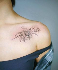Fine line rose tattoo on the left shoulder.